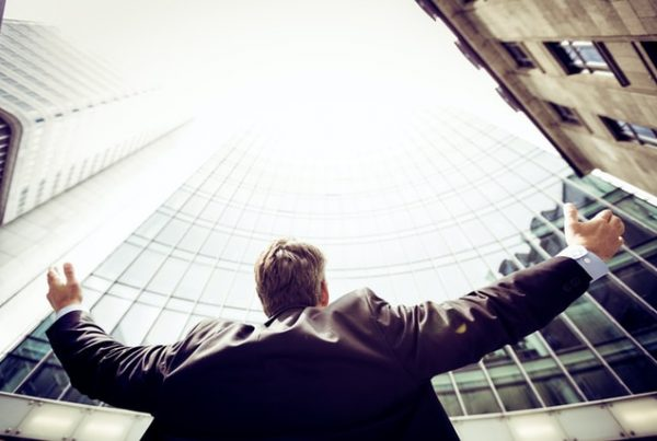 A man looks up at a business building with his arms open. This represents business opportunities